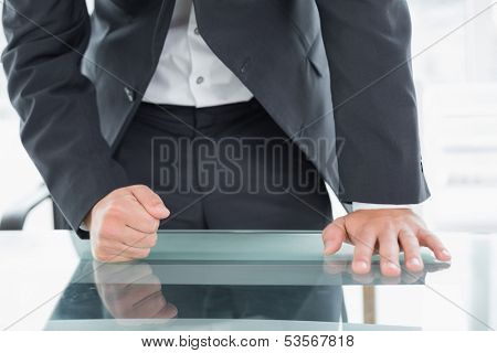 Close up mid section of a well dressed businessman with clenched fist on the desk at office