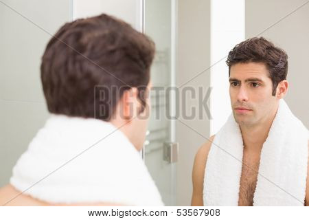 Rear view of a tensed young man looking at self in mirror in the bathroom