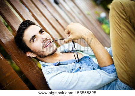 Handsome young man sitting outdoors, looking up with a dreamy expression