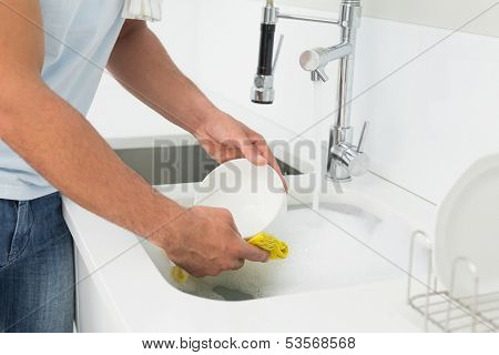 Close up mid section of a man doing the dishes at kitchen sink in the house