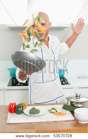 Cheerful young man tossing vegetables in air at the kitchen