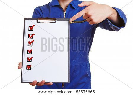 Hand of a construction worker pointing to checklist on a clipboard