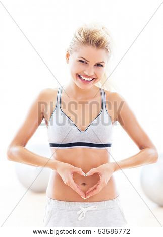 Woman making heart shape around belly button
