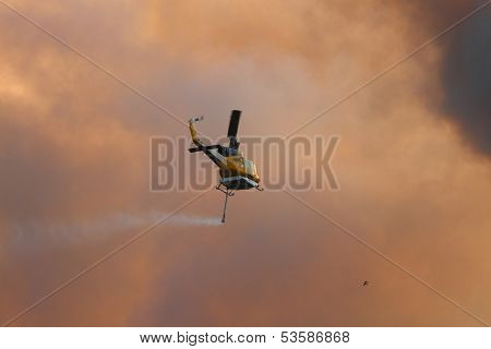 Ningi, Australia - November 9 : Waterbomber Helicopter With Full Load Heading To Fire Front Into Clo