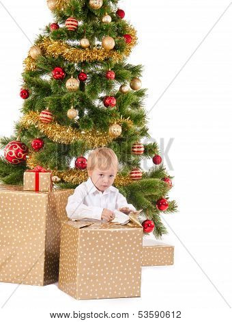 Little Boy Opening Christmas Gift Near New Year's Tree