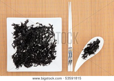 Arame seaweed on a white plate and dish over bamboo with chopsticks.