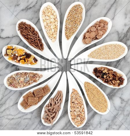 Healthy breakfast cereals in porcelain dishes over marble background.