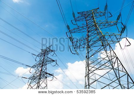 High voltage power transmission towers aganist the blue sky background.