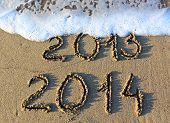 stock photo of outline  - Happy New Year 2014 replace 2013 concept on the sea beach - JPG