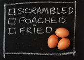 image of scrambled eggs  - Three brown chicken eggs on a blackboard next to tick boxes for your favourite means of cooking such as scrambled - JPG