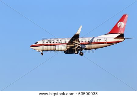 Meridiana Boeing 737-700 aircraft on the blue sky background