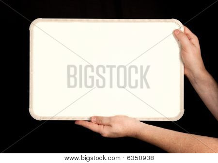 Whiteboard In Man's Hands On Black Background