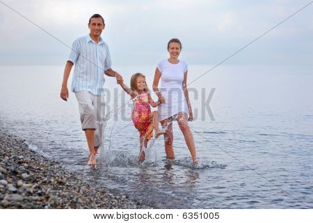 Happy Family With Little Girl Splashes Feet Water On Beach In Evening