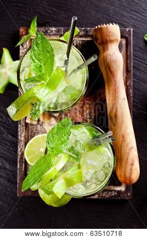 Mojito lime drinks on black stone surface, upper view