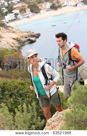 Couple of trekkers climbing island creek