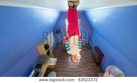 Little girl in jeans stands on the ceiling upside down at inverted house