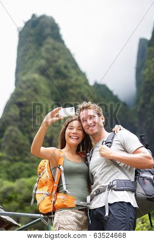 Couple taking selfie self portrait hiking on Hawaii in outdoor activity. Woman and man hiker taking photo with smart phone camera. Healthy lifestyle from Iao Valley State Park, Wailuku, Maui, USA.