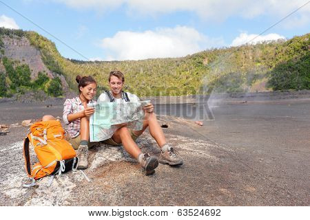 Couple hiking on volcano on Hawaii looking at map. Happy young man and woman relaxing taking break in beautiful volcanic landscape nature on Big Island in Hawaii Volcanoes National Park, USA.