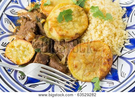 Moroccan sweet potato and beef tagine with couscous, closeup on a plate with a fork. A traditional dish from Fez