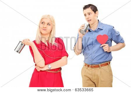 Guy expressing love to an indifferent girl through a tin can phone isolated on white background