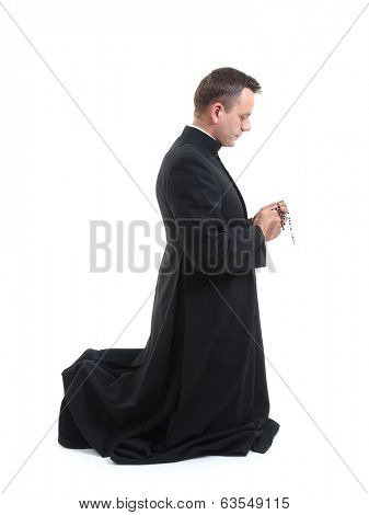 Catholic priest klneeling and saying his rosary beads