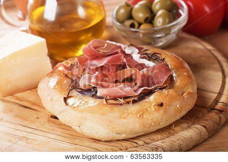 Italian focaccia bread with prosciutto, cheese and green olives