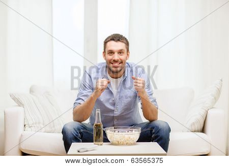sports, happiness and people concept - smiling man watching sports on tv and supporting team at home