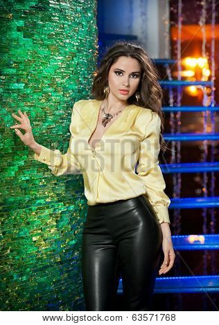 Attractive brunette woman with long hair in elegant yellow blouse and black leather pants in club