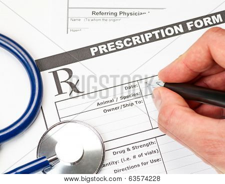 Hand with pen over blank vet prescription form with stethoscope and glasses