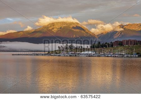 foggy sunrise over Lake Dillon and marina in Colorado with a mountain forest damaged by pine beetle