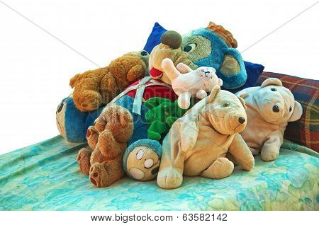 Old Stuffed Animals On A Bed