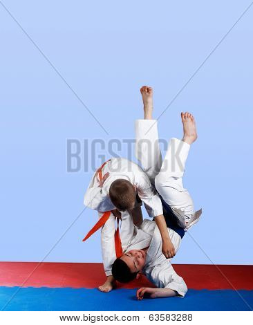Boy with orange belt  done a throw judo