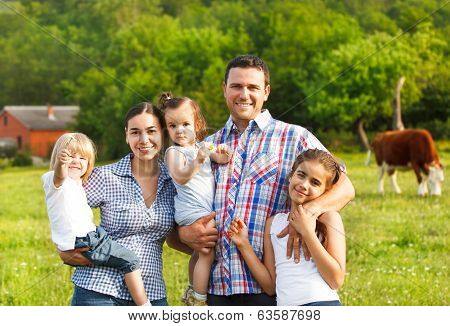 Young Family With Three Children On The Farm