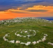 stone circles in mountains on sunset background
