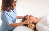 stock photo of reiki  - Professional Reiki healer doing reiki treatment to young woman - JPG