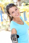 Portrait of smiling fitness girl with music earphones on