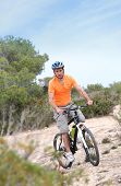 Man riding mountain bike on island trail