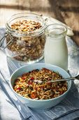 Serving of homemade granola in blue bowl and milk or yogurt on table with linens