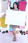 Beautiful young woman holding blank poster near rack with hangers