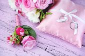 Beautiful wedding bouquet and cushion with rings on wooden background