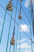 foto of pulley  - Sailboat stainless pulleys and rope details on blue sky with white clouds - JPG