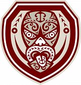stock photo of maori  - Illustration of a traditional maori mask with tongue out facing front set inside shield done in retro style on isolated background - JPG