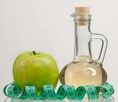 image of cider apples  - Apple vinegar in the glass bottle with fresh apples on a grey background - JPG