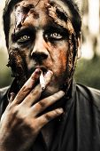 picture of exhumed  - Evil dead zombie smoking cigarette with scary horror expression outdoors - JPG
