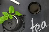 Teapot with herbs and teacup on chalkboard top shot