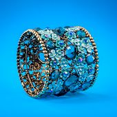 Blue braclet with gems on color background
