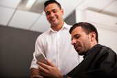 pic of barber  - Handsome barber and a client social networking with a smart phone at a barber shop