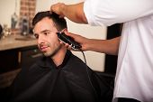 stock photo of barber  - Young Latin man getting his sideburns trimmed by a barber in a barber shop - JPG