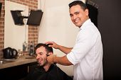stock photo of barber  - Happy young barber trimming a client - JPG