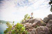 foto of samadhi  - Yoga meditation in yoga pose by woman on the peak of mountain - JPG